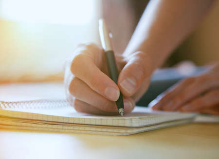 vrouwelijke handen met pen schrijven op notebook Stockfoto