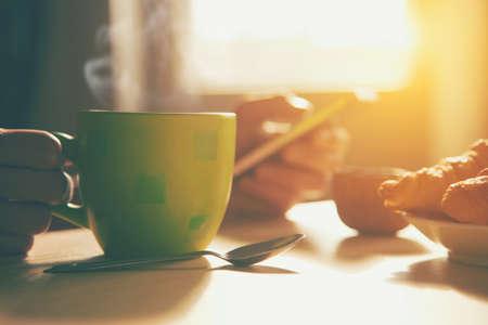 frisches Frühstück mit heißem Kaffee und Browsing-Smartphone in Morgensonnenlicht Standard-Bild