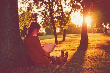 Niña de leer el libro en el parque en la luz del atardecer de verano Foto de archivo - 46674853