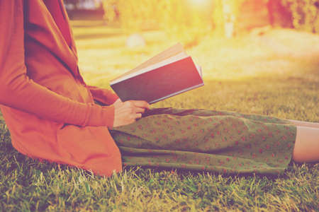 girl reading book at park in summer light Stock Photo