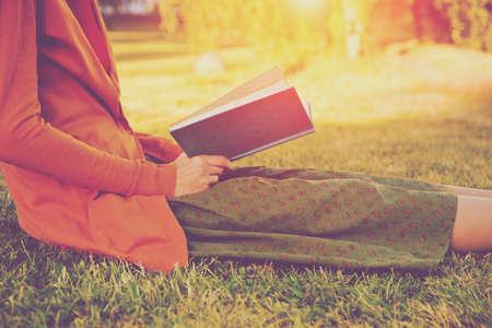 Meisje lezen boek op park in zomer licht