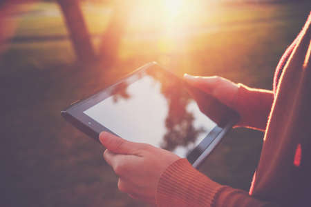 mobile sms: hands holding digital tablet pc in summer sunset light Stock Photo