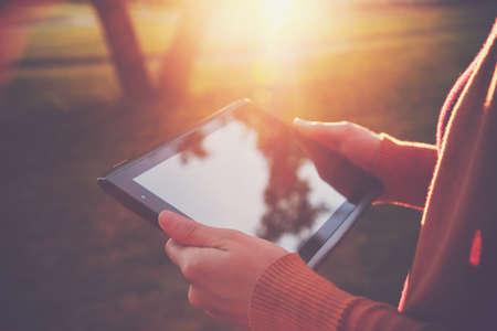 mains tenant pc tablette numérique dans le coucher du soleil la lumière d'été