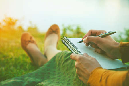 pen and paper: female hands with pen writing on notebook on grass outside Stock Photo
