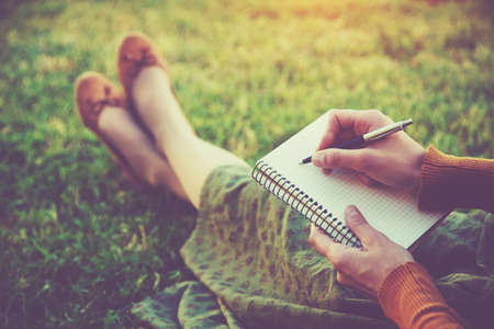 person writing: female hands with pen writing on notebook on grass outside Stock Photo