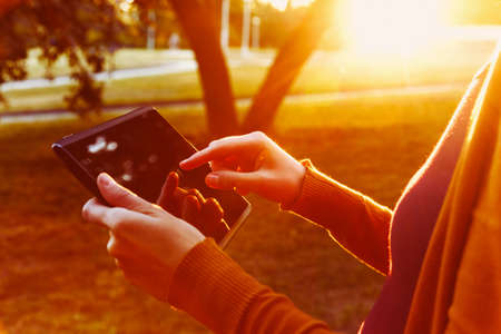 hands holding digital tablet pc in summer sunset light Stock Photo