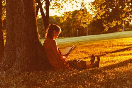 Meisje lezen boek op park in zomer zonsondergang licht