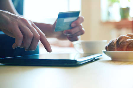 Hands holding credit card and using digital tablet pc with morning coffee and croissant. Online shopping. Banque d'images