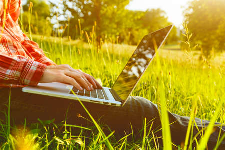 device: Hands using laptop and typing in summer grass Stock Photo