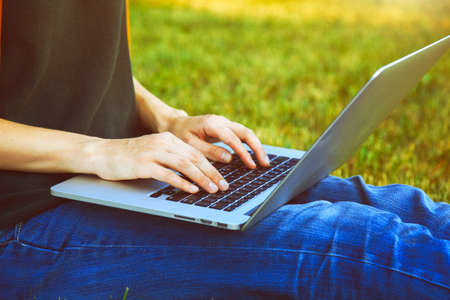 typing: Manos usando la computadora portátil y escribiendo al aire libre en la naturaleza de fondo Foto de archivo