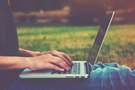 Mains utilisant un ordinateur portable et de taper à l'extérieur sur la nature de fond Banque d'images