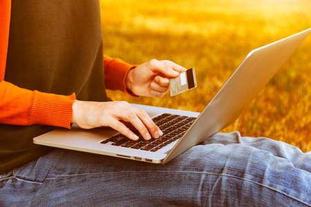 chicas de compras: Manos que sostienen la tarjeta de crédito y usan la computadora portátil en fondo natural del verano. Las compras en línea Foto de archivo