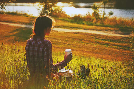 erudition: Girl with coffee cup and book enjoying on summer shore of river