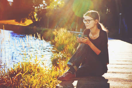 soñando: Muchacha sonriente con la taza de té o café disfrutando en la orilla del río de verano