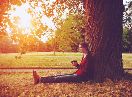 people relaxing: Smiling girl with cup of tea or coffee enjoying near park tree in morning sunlight Stock Photo