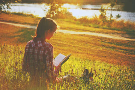 Girl reading book on summer shore of river