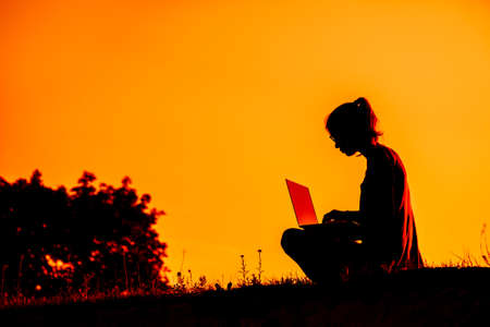 silhouette of a girl with laptop on sunset or sunrise background