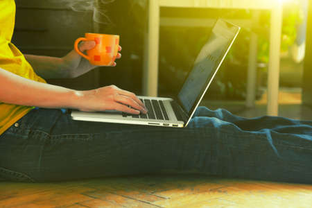 laptop en koffie beker in handen meisjes zitten op een houten vloer Stockfoto