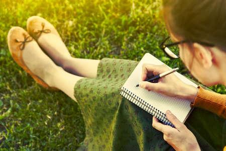 persona escribiendo: chica con la pluma de escribir en el cuaderno en la hierba fuera