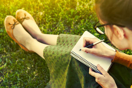 person writing: girl with pen writing on notebook on grass outside