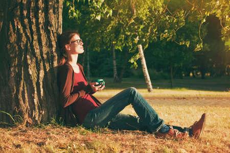 mujer sola: Muchacha sonriente con la taza de té o café disfrutando cerca del árbol de parque en la mañana la luz del sol Foto de archivo