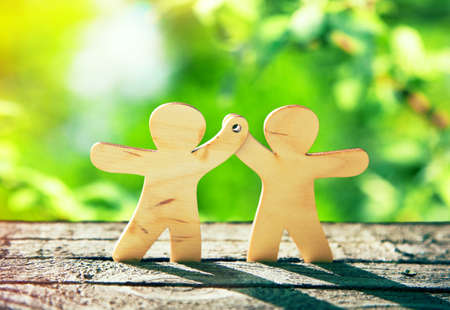 Wooden little men holding hands on natural green background. Symbol of friendship, ecology and teamwork
