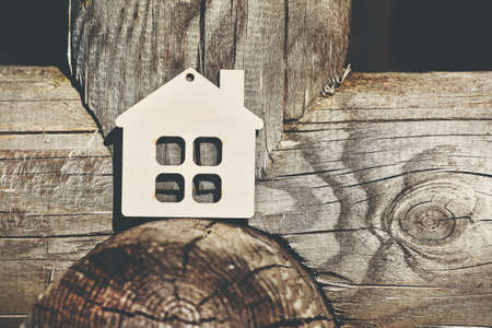 wooden house as symbol on the logs of framework house