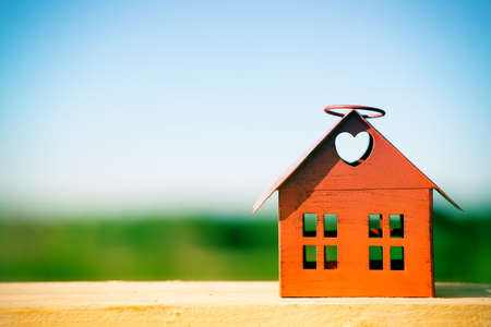 red model of house as symbol on nature background