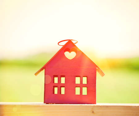 home sale: red model of house as symbol on sunlight background