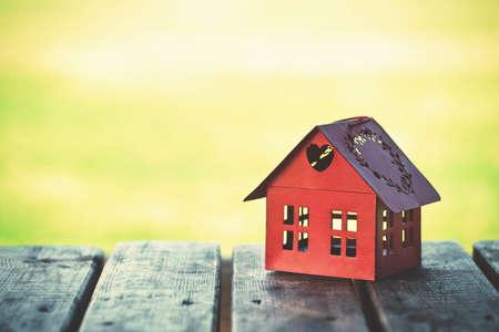 hospedaje: modelo rojo de la casa como símbolo en el fondo de sol