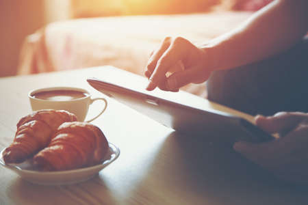 Hands holding digital tablet pc with morning coffee and croissant.