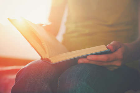 erudition: hands holding book and reading in sunlight