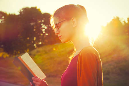 girl reading book in summer sunset light