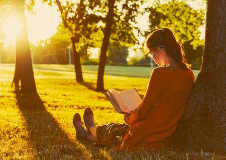 girl reading book at park in summer sunset light Stock Photo