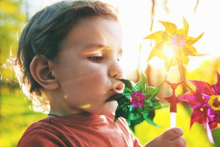 Portrait of a cute boy blowing wind wheel in sunshine Stockfoto