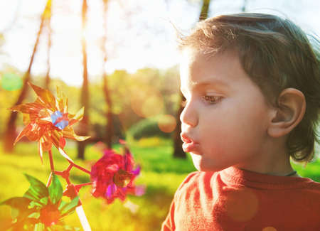 blowing of the wind: Portrait of a cute boy blowing wind wheel in sunshine Stock Photo