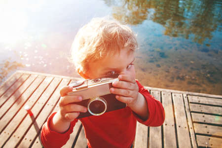 personas tomando agua: Portrait of a smiling cute boy taking picture with retro camera at a lake