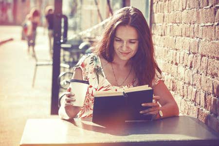 mujer leyendo libro: niña sonriente sentado en una terraza de verano en la calle con el café de la mañana y el libro de lectura