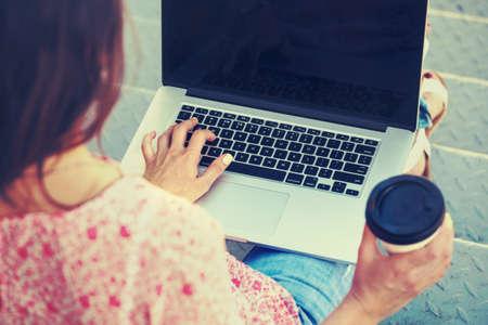 ノート パソコンと階段の階段の上に座ってコーヒーを持つ少女
