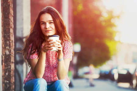 smiling pretty girl sitting in street with morning coffee