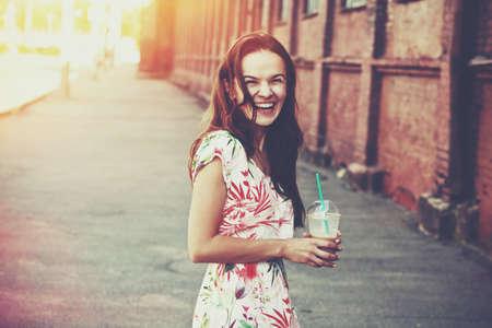 shake off: pretty laughing girl with milk shake walking at morning street