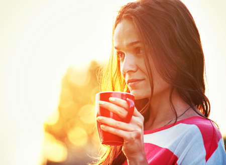 drink coffee: pretty girl with morning coffee at sunrise