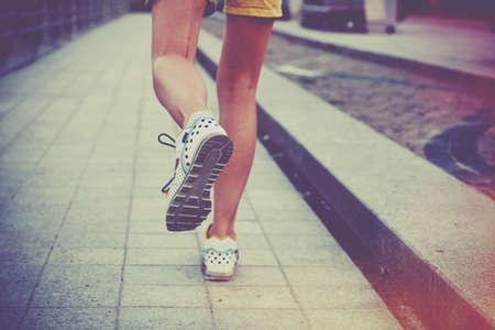 purposeful: Girl jogging in park. Feet running on road