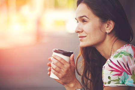 pretty girl sitting in street with morning coffee Standard-Bild
