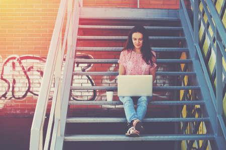 trabajo social: Muchacha bonita que trabaja con ordenador portátil sentado en las escaleras de la escalera Foto de archivo