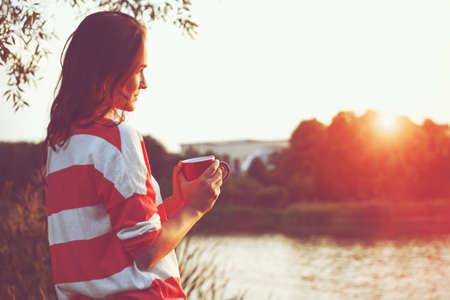sunrise: hübsches Mädchen mit Kaffee am Morgen am Fluss Sonnenaufgang