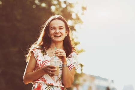 shake off: pretty smiling girl with milk shake walking at morning street Stock Photo