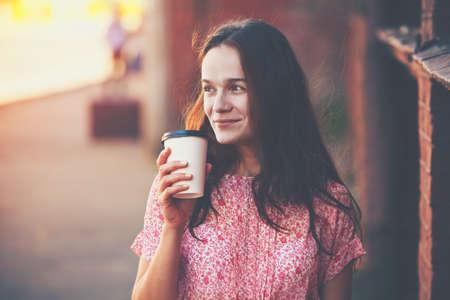 copa: sonriente niña bonita caminando en la calle con el café de la mañana