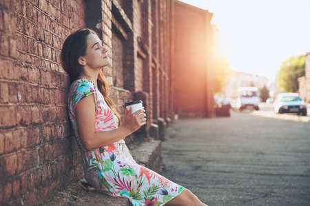 pretty girl sitting in street with morning coffee and relaxing