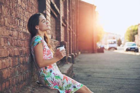 mooi meisje zit in de straat met 's ochtends koffie en ontspannen
